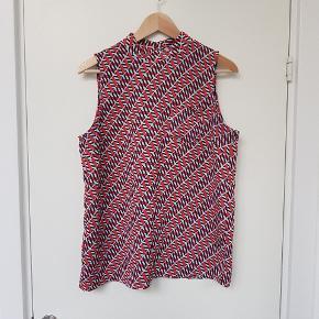 Højhalset mønstret crepetop fra Next med en lille lomme på brystet og knapper i nakken.