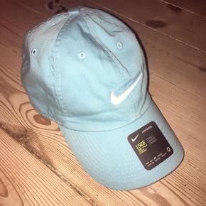 Helt ny lyseblå/turkis cap/kasket fra Nike - den kan justeres i størrelsen bag til med strap.