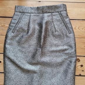 Guld nederdel i polyester fra H&M.  Aldrig brugt.  Str. 34.  Skjult lynlås på bag.  Lommer der kan åbnes hvis man synes. Lige nu er de stukket fast.  Sort foer indeni.  Kan afhentes i Esbjerg eller sendes. Angivet pris er excl. fragt.