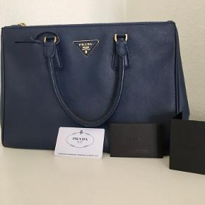 PRADA Galleria Medium læder håndtaske i mørkeblå farve. Måler h24, l32, b13,5 cm. Man kan nemt få ned en normal computer. Med lang rem.  Certificate card kommer med.   Meget god stand undtaget håndtagene. Se billeder, der har den mistet den blå farve. Derfor den lave pris. Se flere billeder neden.   Tasken er købet i Stockholm 2015. Pris i butik: 15.700kr  Saffiano leather Double leather handle Detachable adjustable leather shoulder strap Gold-toned hardware Metal lettering logo on leather triangle Snap closure on sides Two outside pockets with zipper closure Three inside pockets, including one with zipper closure Prada logo lining