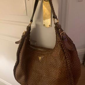 Kærnelæderfarvet taske fra Prada i flettet læder. Tasken er i god stand men i inderforet er der brugstegn. Udenpå kan man slet ikke se at den er brugt, dette skyldes også den flettede struktur.  Tasken har lynlås og et lille rum indeni med lynlås.