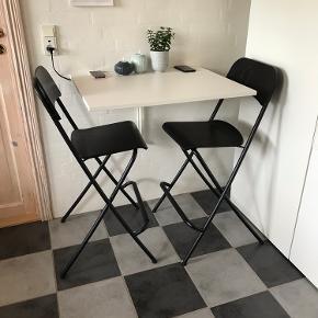 IKEA Norberg barbord (74x60vm) med to stk Franklin (63cm) barstole. Der er i bordet lavet huller til trådløs opladning af telefoner, se billeder. Bort set fra det så fremstår sættet som nyt 😉