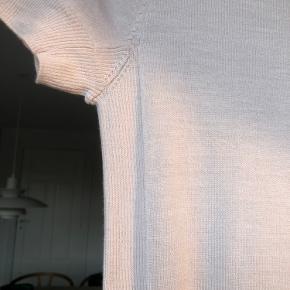 Lækker strikbluse i 100% tynd merinould.  Farven ef lys grå/kit.  Brystvidde 84 cm, længde midt bagpå incl halskant 61 cm