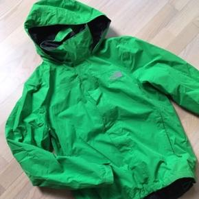 Lækker grøn regnjakke fra North Face i næsten ny stand. Hætten kan pakkes ind i kraven med velcro. Nypris 1000.