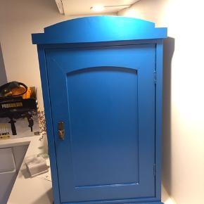 Smukt gammelt træskab som jeg selv har malet blåt.  Mulighed for ophæng på væg   Måler 39 cm lang 63,5 høj og 21,5 dyb  Mangler lille træstykke nederst på højre side (kan ses på billedet)