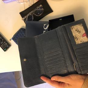 Helt ny pung fra Guess,få brugsstegn på logoet, i form af små ridser. Blå og hvid stribet. Clutch-pung