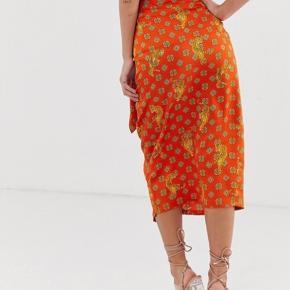 Wrap nederdel fra Never Fully Dressed med tiger print. God stand og lækkert materiale. Kan passes af str. S-M.