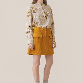 Denne nederdel med lommer foran er fremstillet i en fin og blød fløjlskvalitet. Nederdelen har elastik i livet bagpå og lukkes foran med lynlås og en lille synlig knap.