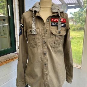 Rigtig flot jakke fra SuperDry ,, lys army farve. Hætten kan knappes af,, den er i grå sweatshirt stof. Skrevet ubrugt, da den kun er brugt en enkelt gang, ingen fejl. Sender gerne mod betaling af porto'en.