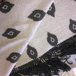 Fin grå plaid med elegant mønster. Fremstår som ny. Den har ingen mangler eller tegn på slid.
