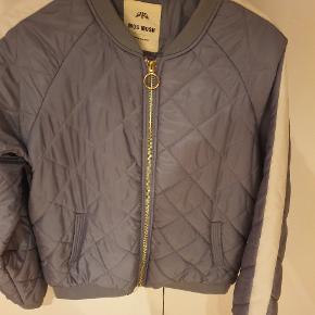 Super fin jakke, fra kendte mos mosh. Sporty og med guldlynlåse. Kommer i begge sider og kontrast stribe på ærmer. Logoskilt i nakken.