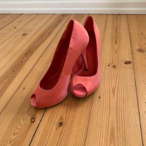 Skoene har en skade på højre hæl fra en stålrist. Begge sko har mindre mærke affarvninger.