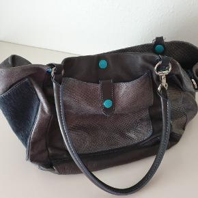 Brand: GABS  Fantastisk taske i blødt læder fra det italienske kvalitetsmærke GABS. Brugt få gange, er som ny, uden mærker. Mange anvendelsesmuligheder. Indeholder også en aftagelig lille indertaske/clutch. Aftagelig rem + indkøbsnet. Nypris 2699kr.