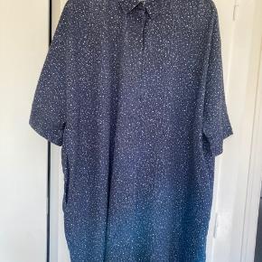 Flot og behagelig oversize kjole med skjult knaplukning foran og stiklommer i siderne.