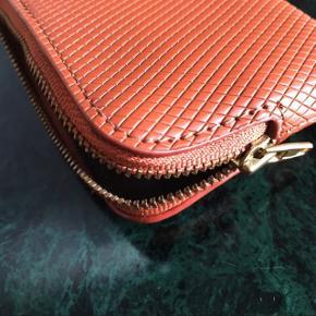 Brun læderpung fra Moss Copenhagen. Pungen er i god stand. Passer til kort. Måler ca. 10 x 8 cm. Nypris: 250 kr.