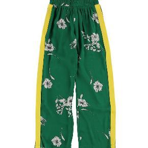 Str M svarer til str 12 år/152  Helt nye løse bukser fra Hound  Smarte Hound bukser i grøn med print af blomster og ned langs siderne er der en gul stribe.  Hound bukserne har en bred elastikkant omkring taljen. Ved benåbningen er der en slids som er med til at giver bukserne en fin detalje. Stoffet er i en tynd og let kvalitet.