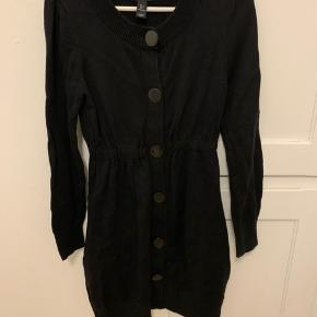 Fin strik cardigan med talje, lommer og store knapper foran til.  Materiale: 100% bomuld