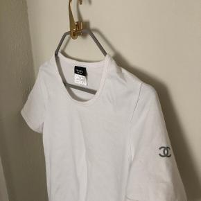 Enkel og klassisk hvid t-shirt fra Chanel med cc-logo på højre ærme.  97% bomuld - 3% elastane. Max iført et par gange, så den fremstår fuldstændig som ny.  Mp 1200,-  Kan sendes med DAO på købers regning eller afhentes i Kbh. K / Frb. C efter aftale.