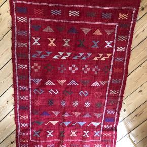 Jeg sælger mit smukke ægte marrokanske kelimtæppe. Tæppet er købt i Marokko for tre år siden - det har været gemt væk længe, men udover lidt støv og almindelig patina fejler det ingenting 💜 Jeg kender ikke det præcise materiale udover, at jeg ved det er uld.   Mål:  Længden er ca 142 cm (med kvasterne)  Og bredden ca 88 cm🪀  Tæppet kan hentes på Nørrebro eller muligvis sendes💜