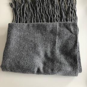 Grå tørklæde. Materiale se foto. Str. 208x75. Kan sendes mod betaling af porto kr. 40,00 med DAO.