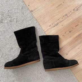 Mentor sorte kvalitets vinter sko i lammeskind og ruskind. Disse støvler er meget varme, da de er foret med lammeskind (hele vejen op til tæerne) - så hvis du har kolde fødder, er disse sko noget for dig. De måler omkring 24cm indeni. Brun bund. Fremstår i flot stand men med små tegn på brug her og der, se billeder.   Søgeord: pels, støvler, støvletter, boots, winter, lamb fur, snow