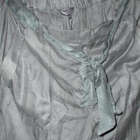 HELT NYE bukser i 100% Viscose, meget bløde og behagelige at have på.  Har bredt elastik bagpå, så de er meget fleksible i størrelsen. Har yderligere et pyntebindebånd, men kan sagtens bruges uden.  Farven er en varm støvet grøn.  Se også mine flere end 100 andre annoncer med bla. dame-herre-børne og fodtøj