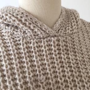 Lækker lang sweater med hætte i stort strik.  Brugt 1 gang. Men har en trukket tråd - se billede.