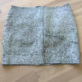 Varetype: Andet Farve: Grå,  Hvid,  Sort  Rigtig fin nederdel i krakeleret skind - aldrig brugt.