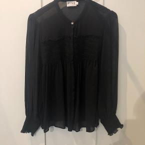 Fin skjortebluse med smockdetalje ved brystet og på ærmerne. Blusen er størrelsessvarende.  Aldrig brugt, kun vasket.  BYTTER IKKE!
