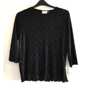 Bluse med masser af stræk. 3/5 ærmer. Brystvidde: 60 cm. X 2 uden at strække stoffet. Længde: 68 cm.