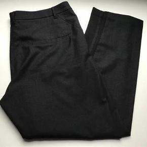 Flotte bukser  Meget mørkegrå ( nærmest sorte )  Aldrig brugt  Livvidde ca 2 x 48 cm  Indvendig benlængde ca 74 cm   65 % uld  15 % viskose 17 % polyester  3 % lycra  Bukser Farve: Mørke grå Oprindelig købspris: 998 kr.