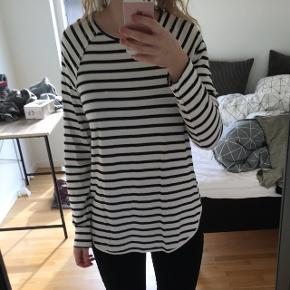 Langærmet bluse/tunika med sorte og hvide striber. Brugt, men dette kan ikke ses  Kan afhentes i Give. Hvis pakken skal sendes, skal køber betale fragten