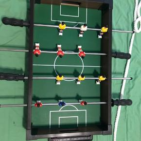 Mini bordfodbold med 6 spiller på hver hold, 4 pinde med 3 spiller på hver, bordet er uden ben. Mål; L:59 H:9,5 B:31 Mini bordfodbold er i pæn stand, det er næsten ikke blevet brugt og derfor sælges dette. Kommer fra ikke-ryger hjem. Sender gerne, men på modtagers regning. Varen er i Århus V.