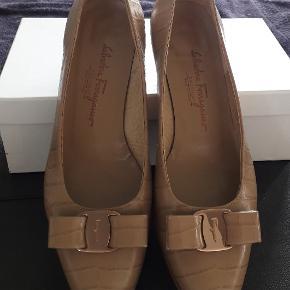 """Lysebrun kroko printet pump i 100 % læder.  Skoene er uden pletter, men der er 2 små ridser over venstre hæl (Ca. 1*3 mm). Ridserne ses på 2 sidste billede """"close-up"""" og på sidste billede med 1 mtrs afstand. Modellen hedder Vara og er deres klassiske model i skind, denne med skindsløjfe. Vara modellen kan ses hos Ferragamo.com som """"vara bow pump shoe"""" Jeg har dem i flere farver og stand.  Jeg har ikke æsken. Da jeg har købt dem i udlandet og transporteret dem som hånd bagage.  Størrelsen er 8,5 B eller C. man kan ikke se det i skoen. Det er gnedet af, men jeg tror , at det er B. Ferragamo syntes det er en 39,0. Men jeg mener det svarer til en 38,5.  Skoens Mål: Længde 26 cm. Den bredeste del af forfoden 8 cm. Hælhøjde 3 cm."""