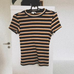 Stribet tæt t-shirt fra Monki i farverne: Navy, karry og hvid. Super flot, og ingen pletter el. lign. 🤍