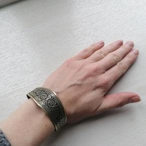 Håndlavet armbånd. Justerbar og formbar alt efter håndled. Ved ikke hvilket materiale det er lavet i.   2,5 cm hvor det er bredest.  Kan afhentes i Esbjerg. Sender gerne - køber afholder fragt og ansvar.