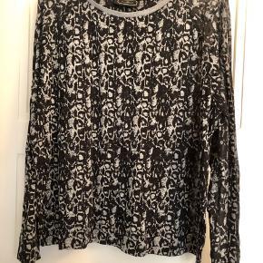 Lækker oversize bluse i grå/sort mønster - er let gennemsigtig.  65% bomuld, 35% polyester.  Model: Izzina.  Bytter ikke!