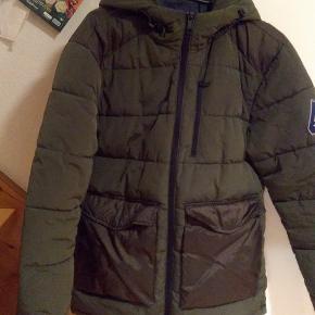 Jakken er brugt få gange, da min søn købte  en anden jakke på udsalg, som han havde drømt om. Han er 168 cm og vejer 68 kilo den passer ham perfekt. Der er vindfang i ærmet. Den er vandafvisende. Justerbar hætte. Varmt foer i lommer. Super jakke.