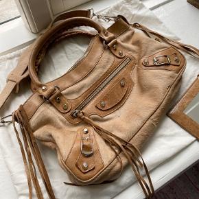 Jeg rydder ud i min taskesamling og sælger derfor min Balenciaga First taske i brunt ponyhår. Tasken bærer præg af brug, som vist på billederne, men den er i god stand. Spejl og dustbag medfølger 🤎