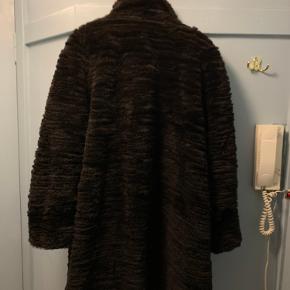 Fantastisk blød pelsfrakke perfekt til at holde varmen i den kolde tid. Frakken er i syet af små baner af pels, der giver den er særlig flot struktur i pelsen. Frakken lukkes med knapper og har satin for.