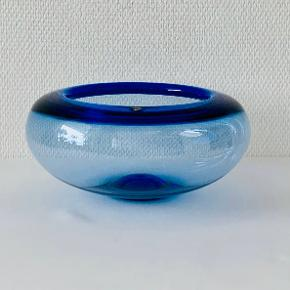 Da Per Lütken designede Provenceskålen i 1955, skabte han samtidig en klassiker i dansk glaskunst.  Den blå skål med en diameter på 25 cm er i mundblæst glas og frit formgivet i hånden.  Brug den som et lille stykke luksus i hverdagen, som frugtskål, til servering af salat - eller som et dekorativt indslag i vindueskarmen. En god gaveide, der kan gå i arv i generationer.  Hvert stykke mundblæst glas er unikt og håndlavet af glaspusteren, som omhyggeligt blæser den rigtige mængde luft gennem den smalle pibe. Luftbobler i glasset er derfor uundgåelige og udgør en del af den charme, der kendetegner mundblæst glas.  Farve: Blå Materiale: Mundblæst glas Diameter: 25 cm