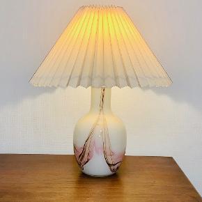 """Sjælden og flot Cascade bordlampe fra Holmegaard, designet ca. 1970 af Per Lütken (1916-1998). Lampe i opalglas med farvede flusser, der under bearbejdning smelter og danner uforudsigelige mønstre. Overfang i krystalglas. Cascade blev formgivet som en reaktion på det """"perfekte"""" ensartede glas, men var for dyrt og besværligt til en stor produktion. Ses ikke ofte. Højde med fatning: 340 cm Højde til fatning: 32,5 cm Diameter: 19 cm Signeret: Nej Prisen er excl. skærm"""