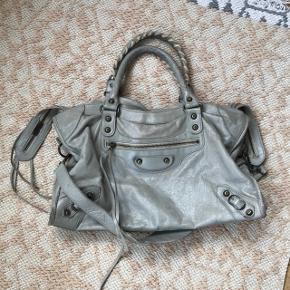 Jeg rydder ud i min taskesamling og sælger derfor denne Balenciaga City taske i grå/beige 😊 Tasken er brugt, og det kan ses, men den har stadig mange år tilbage i sig. Tasken sælges som set - der medfølger ikke dustbag m.m.