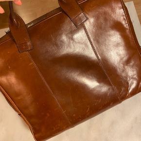 Lækker PC taske fra Tiger of Sweden i brunt kalveskind.   Tasken er brugt en del og har patina, samt er lynlås itu og bør skiftes.   Tasken måler B 38 H 31 D 5,5 cm  Tags: taske mappe computertaske