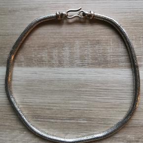 Flot slangekæde i massivt sølv. Måler 43 cm. Vejer 100 g. Diameter 6 mm. Flot uden skader eller fejl, trænger til en pudsning.