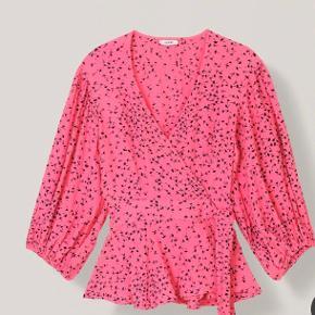 Den kendte ikoniske pinke slå-om Crepe Barra bluse fra Ganni. Helt ubrugt . Sælges kun idet købt i forkert str .