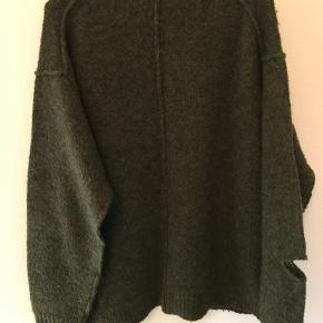 Skøn, uhøjtidelig grøn sweater i uld, lidt oversize model. Sweateren er født med huller forskellige steder og i forskellige størrelser.Den er ikke brugt meget, så den fremtræder pæn.