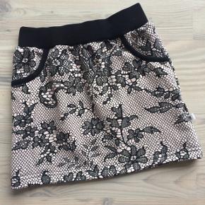 Fra egen systue: Nederdel i let stretchisoli med elastik- og ribkant foroven. Nederdelen har 2 små lommer i siderne. Den er super nem at tage af og på. Kan bruges alene i sommervarmen, eller med et par leggings eller strømpebukser under. Materialerne er let stretchisoli og bomuldsrib. Pudderfarvet baggrund med sort blondemønster. Sort ribkant. Det anbefales at vaske tøjet ved 30 grader og undgå tølet tørretumbling.  Str. 98. Eget mærke: Vibserarius