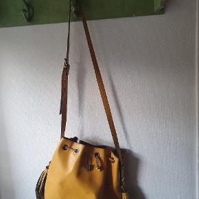 Smuk gul taske. Skulderremmen fejler intet, men snoren (der lukker taske) er slidt. Der er en lukkeknap i tasken.