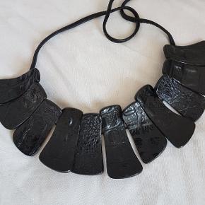 Et fantastisk flot smykke fra Monies. Ved ikke hvad materialet er, men plader med struktur, der bindes med flot lædersnor. Sort/ meget mørkbrun.